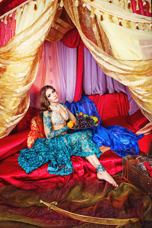 arabian harem: Oriental beauty sitting in a tent and holding a fruit platter. The concept of the Arab harem.