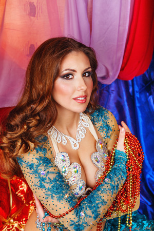 harem: Oriental beauty sitting in a tent and holding a multicolored beads. The concept of the Arab harem.