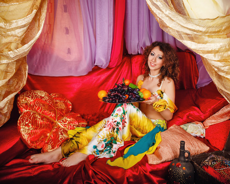 arabian harem: Young oriental beauty sitting in a tent and holding a dish with ripe fruit. The concept of the Arab harem. Stock Photo