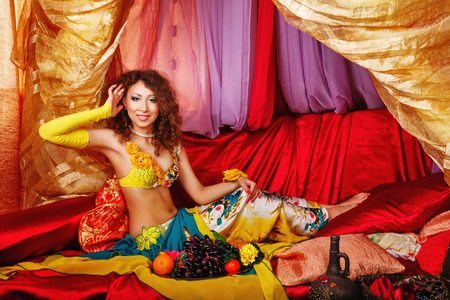arabian harem: Young oriental beauty sitting in the tent, and straightens her hair. The concept of the Arab harem.