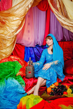 arabian harem: Young oriental beauty sitting in a tent and holding a jug of wine. The concept of the Arab harem. Stock Photo