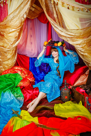 arabian harem: Young oriental beauty sitting in a tent and holding on her head a dish with fruits. The concept of the Arab harem. Stock Photo