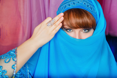 Young oriental beauty hides her face veil. The concept of the Arab harem.