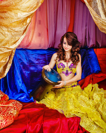 arabian harem: Young oriental beauty sitting in the tent, and plays a pleasant melody on the tabla. The concept of the Arab harem. Stock Photo