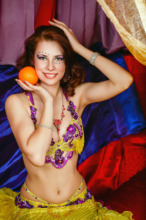 arabian harem: Young oriental beauty sitting in a tent and holding an orange. The concept of the Arab harem.