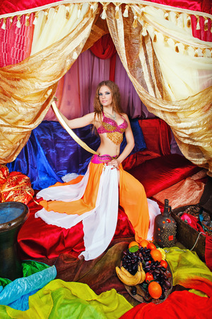 arabian harem: Sexy oriental beauty in a tent and sword in hand abuts her hip. The concept of the Arab harem.