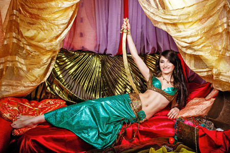 arabian harem: Sexy oriental beauty is in the tent on the pillows and a sword in her hand rests on her hip. The concept of the Arab harem. Stock Photo