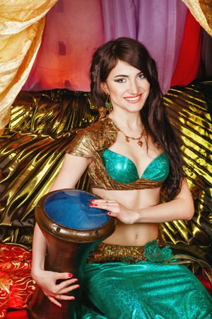 harem: Sexy oriental beauty plays the tabla pleasant melody. The concept of the Arab harem.