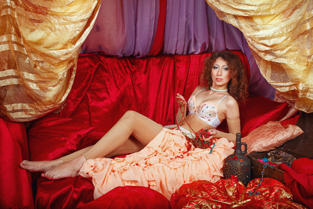 arabian harem: Sexy oriental beauty is in the tent on the pillow and holding jewelry. The concept of the Arab harem.