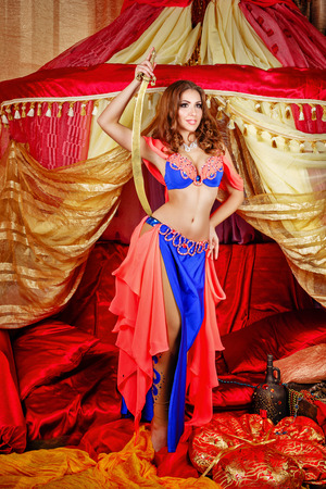 arabian harem: Sexy oriental beauty dancing with a sword in front of a tent. The concept of the Arab harem.