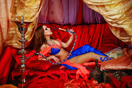 Sexy oriental beauty is in the tent on cushions and smoking hookah. The concept of the Arab harem.