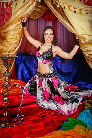 arabian harem: Sexy attractive oriental beauty invites the tent. Hookah is standing next to a tent. The concept of the Arab harem. Stock Photo