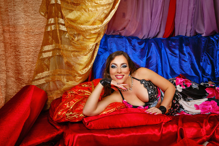 harem: Sexy attractive oriental beauty lies invitingly on pillows. The concept of the Arab harem. Stock Photo