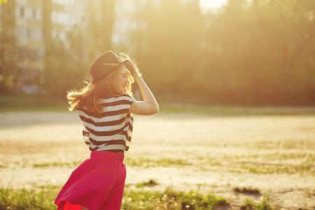 Portrait of a girl in a hat walking in a city park. Foto de archivo