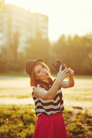 Young attractive girl in the hat makes self on a cellphone. The concept of urban street youth fashion. Communication in social networks. photo
