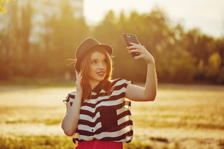 Young attractive girl in the hat makes self on a cellphone. The concept of urban street youth fashion. Communication in social networks. Foto de archivo