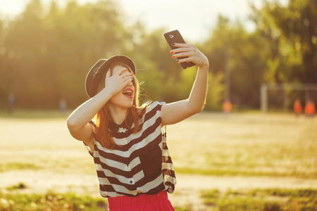 Young attractive girl in the hat does cheerful selfei on a cellphone. The concept of urban street youth fashion. Communication in social networks.