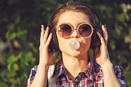 audifonos: Chica inconformista joven que escucha la música en los auriculares en un parque de verano. Retrato de primer plano con la goma de mascar. Tonificación caliente. El concepto de juventud alegre.