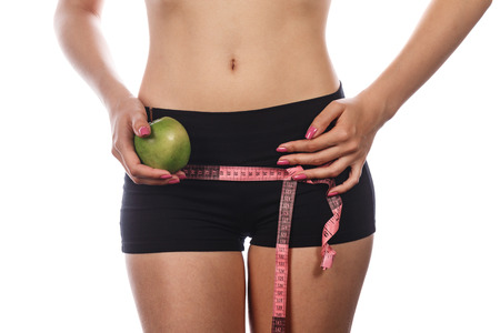 hunker: Slim athletic girl measuring buttocks and holding an apple. Isolated on white background. The concept of healthy nutrition and sport lifestyle.