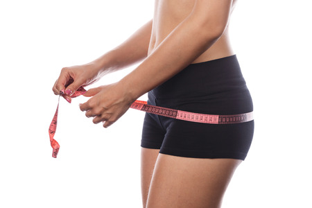 hunker: Young slim woman measures buttocks. Side view. Isolated on white background. The concept of weight loss.