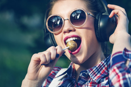 Young hipster girl listening to music on headphones in a summer park. Close-up portrait with a lollipop on a stick. Warm toning. The concept of carefree life.