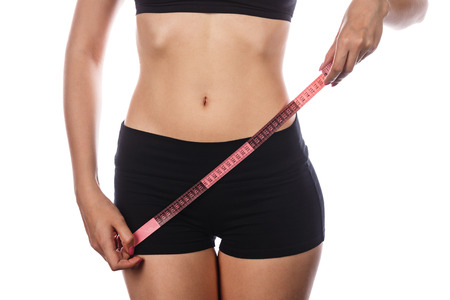 excess weight: Young slim woman holding a measuring tape in front waist. Isolated on white background. The concept of losing excess weight.