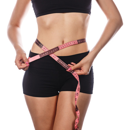 excess weight: Young slim girl measuring waist. Isolated on white background. The concept of losing excess weight.