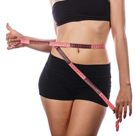 Young slim woman measuring waist circumference and shows a thumbs up after a diet. Isolated on white background. The concept of excess weight loss and healthy eating.