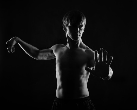 key punching: Kung Fu athlete shows the self-defense techniques. Low key. The concept of self-defense without weapons.