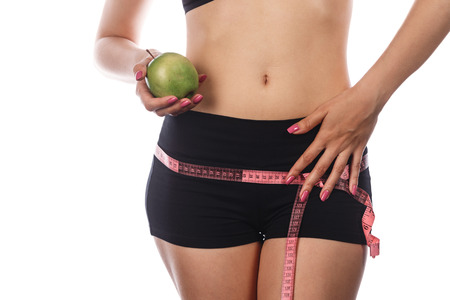 hunker: Young slim athletic woman measures buttocks and holding an apple. Isolated on white background. Concept of healthy food. Stock Photo