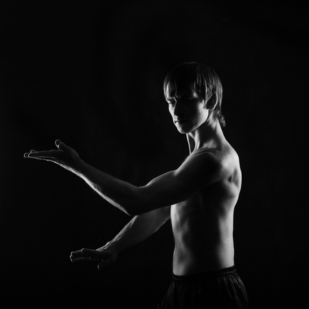 key punching: Male fighter kung fu doing kata. Low key. Dramatic portrait. The concept of male power.