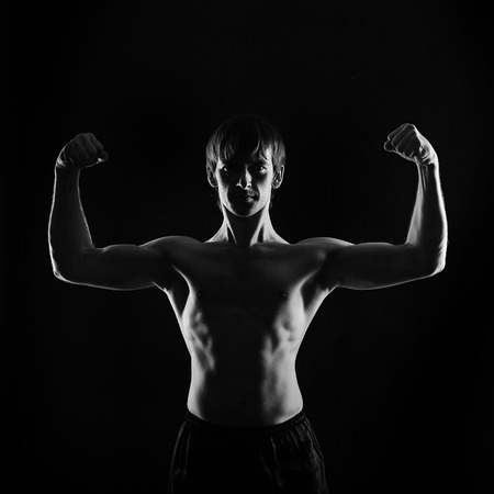 key punching: Male fighter frontal photo. Low key. The concept of male power.