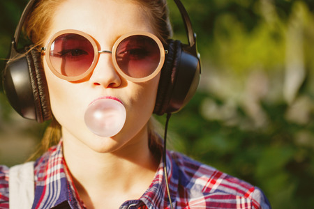 Young hipster girl listening to music on headphones in a summer park. Portrait close-up with chewing gum. Warm toning. The concept of cheerful youth. Standard-Bild