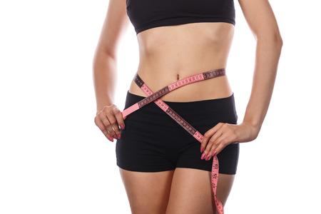 donne obese: Giovane donna sottile misurazione vita dopo una dieta. Isolato su sfondo bianco. Il concetto di perdita di peso in eccesso e una sana alimentazione.