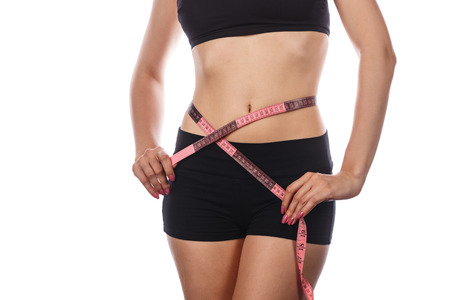 Young slim woman measuring waist after a diet. Isolated on white background. The concept of excess weight loss and healthy eating.