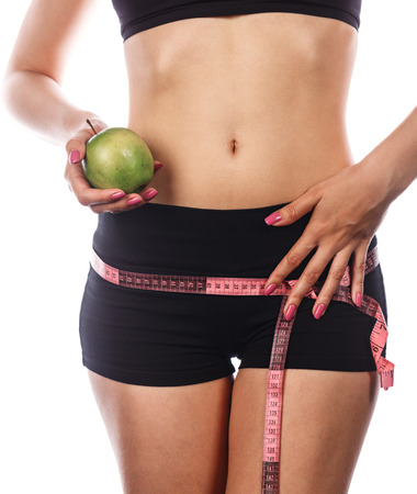 hunker: Slim athletic girl measuring buttocks and holding an apple. Isolated on white background. Concept of healthy food.