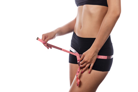 hunker: Young slim athletic woman measures buttocks. Side view. Isolated on white background. Concept of healthy food.