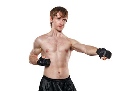enforcer: Male fighter in mixed martial fighting gloves kick. Isolated on white background. Healthy lifestyle concept. Stock Photo
