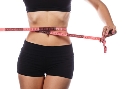 excess weight: Young slender woman measuring her waist after dieting and exercise sports. Isolated on white background. The concept of excess weight loss and healthy eating.