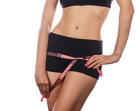 hunker: Young slim athletic woman measures buttocks. Front view. Isolated on white background. The concept of weight loss diet.