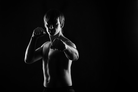 key punching: Male fighter kung fu doing kata. Low key. Dramatic portrait. Space for text. Healthy lifestyle concept.