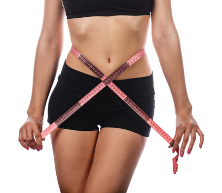 excess weight: Young slim woman measuring waist circumference, following a diet and sports exercises. Isolated on white background. The concept of excess weight loss and healthy eating.