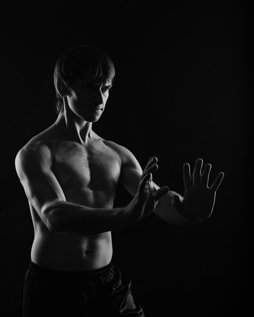 kata: Kung Fu athlete shows exercises breathing exercises. Low key. The concept of martial arts.