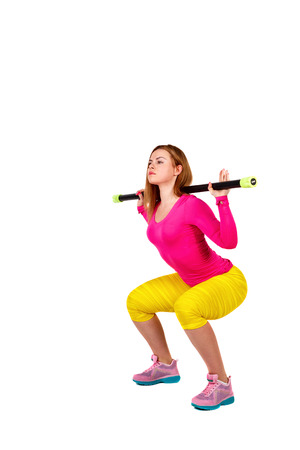 Young athlete squats with fitbar isolated on a white background. The concept of sports fitness lifestyle. photo