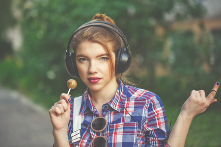 Portrait of pretty attractive girl hipster headphones and a lollipop. Warm toning. The concept of youth fashion.