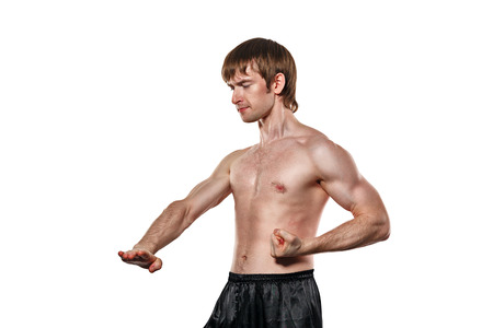 enforcer: The man trains kata kung fu block lower kick. Isolated on white background. The concept of masculine strength and a healthy lifestyle.