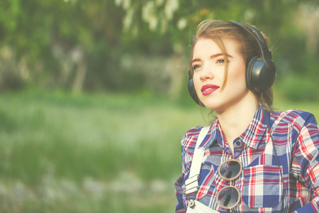 Portrait of pretty attractive hipster girl headphones. Warm toning. The concept of youth fashion. Stock Photo