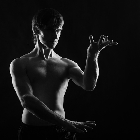 Kung Fu athlete shows the self-defense techniques. Low key. The concept of mind control over the body.
