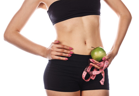 excess weight: Young slim woman holding a measuring tape and green apple. Isolated on white background. Concept of healthy food and the control of excess weight.