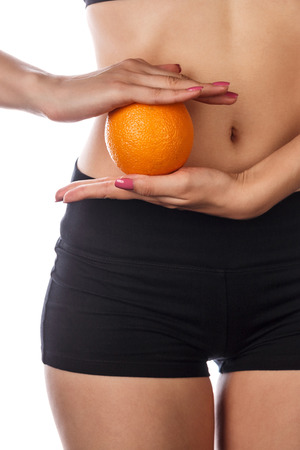 Young slim girl holding an orange near the abdomen. Beautiful skin sport belly. Isolated on white background. The concept of a healthy diet and weight loss diet.